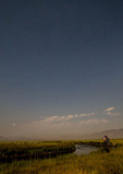 Man photographs stars at Owens River near Mammoth Lakes, CA, at night. The Big Dipper is visible.