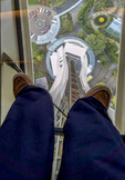 View through the glass floor of the Space Needle's elevator  tower through the feet of someone standing on the glass.