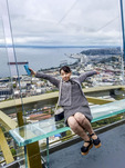 Visiting Japanese woman poses for a picture at the Seattle Space Needle observation deck.