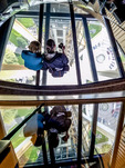 "Two girls look at view down the ""Oculus Stairs"" that link the  observation level and glass floor of the Seattle Space Needle."