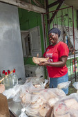 Woman cuts fish filets that will be cooked and sold at the famous fish market at Oistins.