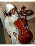 "Woman playing the part of a house slave providing chamber music during recreation of a dinner with ""George Washington."""