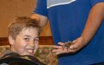 """Young boy, a guest at White Stallion Ranch giggles while Phil Garcia shows him a tarantula during the evening """"Critter Show."""""""