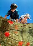 Children explore a tidepool with orange sea bats on the coast of Monterey Bay near Point Pinos, California.