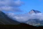 Mt. Gould in morning fog, Common Ravens soaring above ridgeline, viewed from Many Glacier area