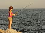 Woman Fishing on Rocks