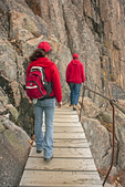 Two hikers on Precipice Trail Wooden Footbridge, Metal Railing, Mt. Champlain, Acadia National Park, Maine
