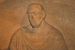 Man from Aquae Sulis, Roman gravestone, Carving of a man wearing a cloak fastened by a brooch, Roman Baths, Bath, England, United Kingdom