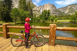 Bicyclist on Swinging Bridge Viewing Yosemite Falls, Yosemite Valley, Yosemite National Park, California
