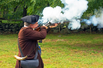 American Revolutionary Colonial Soldier Reenactor Firing Musket, Colonial America, Minuteman National Historical Park, Lexington, Concord, Massachusetts
