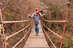 Hiker on Wooden Suspension Bridge, Las Cahorros, Monachil River Gorge, Sierra Nevada National Park, Province of Granada, Andalucia, Monochil, Spain