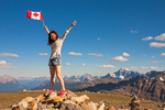 Hiker Holding Canadian Flag on Whistlers Mountain Summit, Jasper National Park, Alberta, Canada