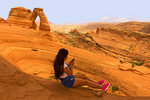 Woman on Cell Phone at Delicate Arch, Arches National Park, Colorado Plateau, Moab, Utah