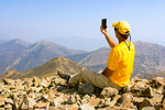 Hiker with Cell Phone on Avalanche Peak Summit, Absaroka Range, Yellowstone National Park, Wyoming