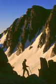 Climber below granite cliffs