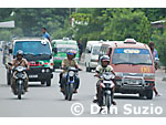 Traffic on a busy street in Dili, Timor-Leste (East Timor). Owners of taxis, trucks, and other vehicles give them names and often elaborate paint jobs to attract customers.