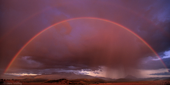906500010 panoramic view of a double rainbow just as the clouds start to break amid a clearing storm right over mount shasta still hidden by cloud cover in the northcentral part of california. extensive coverage of numerous north american parks and other geographic locations.