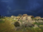 712000043 an ominous dark sky gives way to a rainbow over boulders and grassland in the higher elevations of anza borrego desert state park in southern california. extensive coverage of numerous north american parks and other geographic locations.