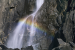 799451470 intimate detail of a waterfall where the light on the water flowing over granite rocks creates a rainbow at the base of Yosemite Falls in Yosemite National Park, California. Extensive coverage of numerous North American parks and other geographic locations.
