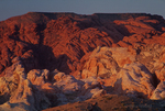 792980013 low angled sunset light highlights the sandstone formations and red rock mountains giving a three dimensional effect to the scene in valley of fire state park nevada. Extensive coverage of numerous North American parks and other geographic locations.