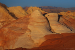 792980034 low angled sunset light highlights the sandstone formations and red rock mountains giving a three dimensional effect to the scene in valley of fire state park nevada. Extensive coverage of numerous North American parks and other geographic locations.