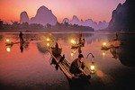 Li River cormorant fishermen at dusk lighting lanterns on their bamboo rafts