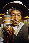 Tibetan in Lhasa's Jokhang Temple, pilgrim with prayer wheel
