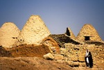 Harran beehive houses, with local Arab man passing by creating Biblical scene, in location where bread originated and once a stop on the Silk Road