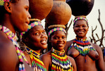 Zulu maidens wearing traditional beadwork and carrying pots on heads at Shakaland