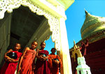 Bagan's Shwezigon Pagoda with novice monks holding alms bowls