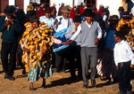 Lake Titicaca retirement celebration for government official with the retiree wearing gifts from constituent admirers