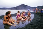 Antarctic tourists from cruise ship enjoying black sand beach and thermal hot springs in the volcanic caldera of Deception Island