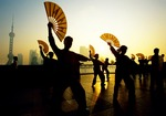 Shanghai Bund morning exercise team with fans at dawn, Pudong skyline in background