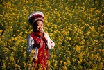 Yunnan's Bai nationality woman in traditional dress in rapeseed field in spring