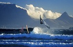 Cape Town windsurfer flips on Big Bay with Table Mountain in background.