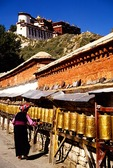 Potala Palace being circumambulated by a Tibetan Buddhist pilgrim turning prayer wheels