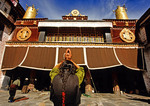 Jokhang Temple with Tibetan Buddhist woman prostrating at entrance
