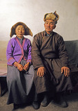 Mongolian farm couple in their farmhouse on Hulun Buir grasslands in northeast Inner Mongolia