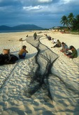 Hainan island fishermen mending nets on the beach next to the South China Sea