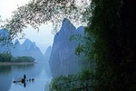Li River cormorant fisherman on bamboo raft framed by overhanging bamboo and karst peaks near Yangshuo (Guilin area)