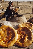 Turkmen woman baking bread in outdoor oven