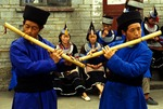 Guizhou's Tall-pointed Hat Miao men in traditional dress playing bamboo flutes