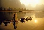 Li River cormorant fisherman on his bamboo raft using net near Yangshuo (Guilin area)