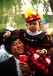 Beijing man carrying his child in the Yuan Ming Yuan park during a summer festival
