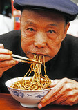 Elderly Chinese man eating noodles with chopsticks in Wuhan