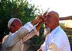 Xinjiang Uygur barber giving shave to customer in Shan Shan county near Turpan on ancient Silk Road