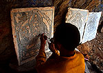 Novice Tibetan monk carving scripture onto stone tablets to be used in construction of a new stupa