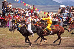 Tibetan horse race at  local festival on grasslands at Damxiong with young jockeys