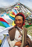 Tibetan Khampa man with prayer flags near Damxiong