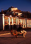 Gyantse shops and dzong (old fort) above street with horsecart in early morning light